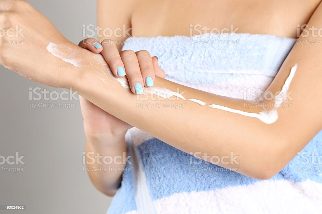 Woman applying cream on hands after shower stock photo