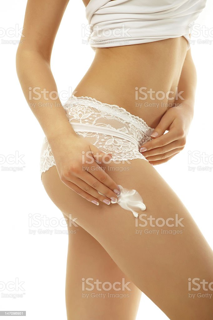 Woman applying cream on her body royalty-free stock photo