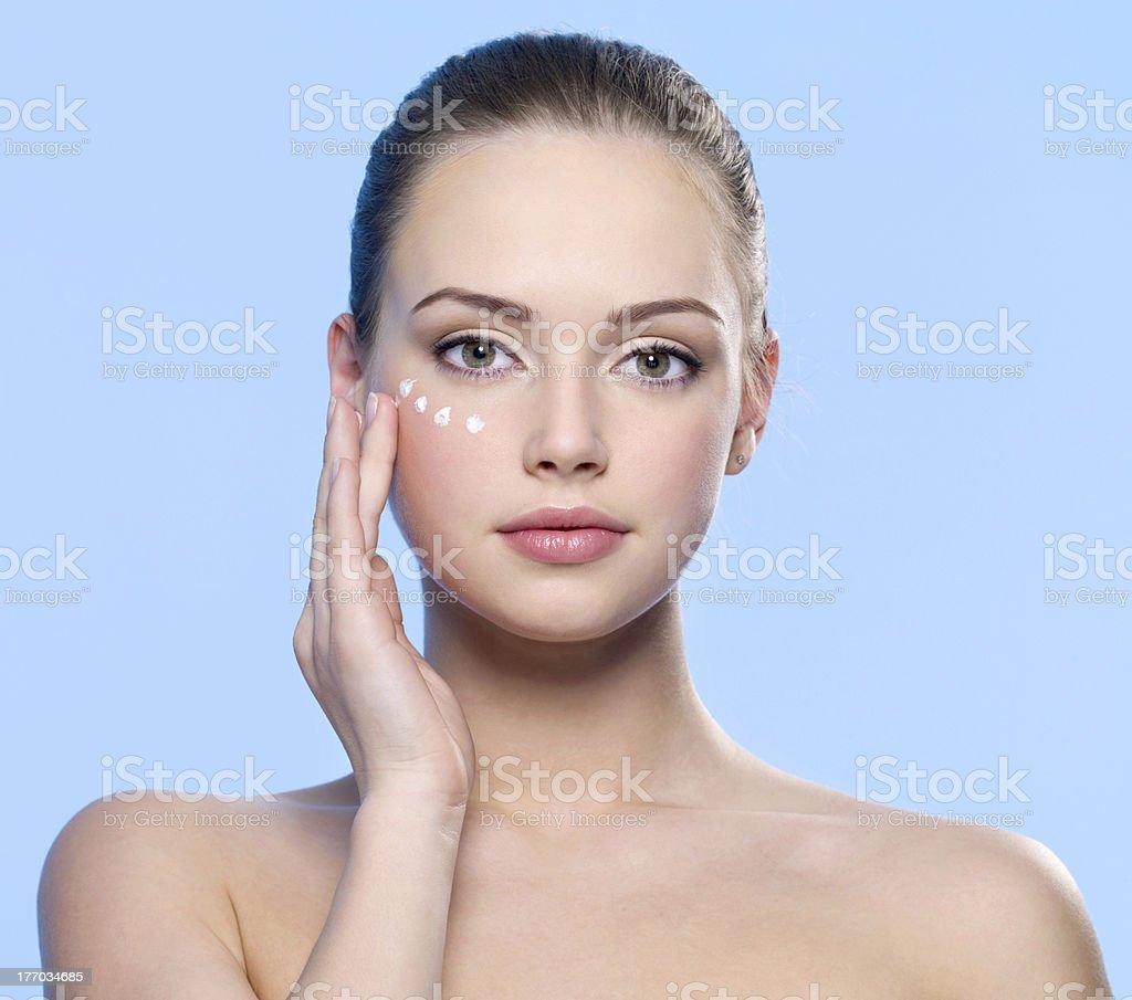 woman  applying cream on her  skin around eyes stock photo