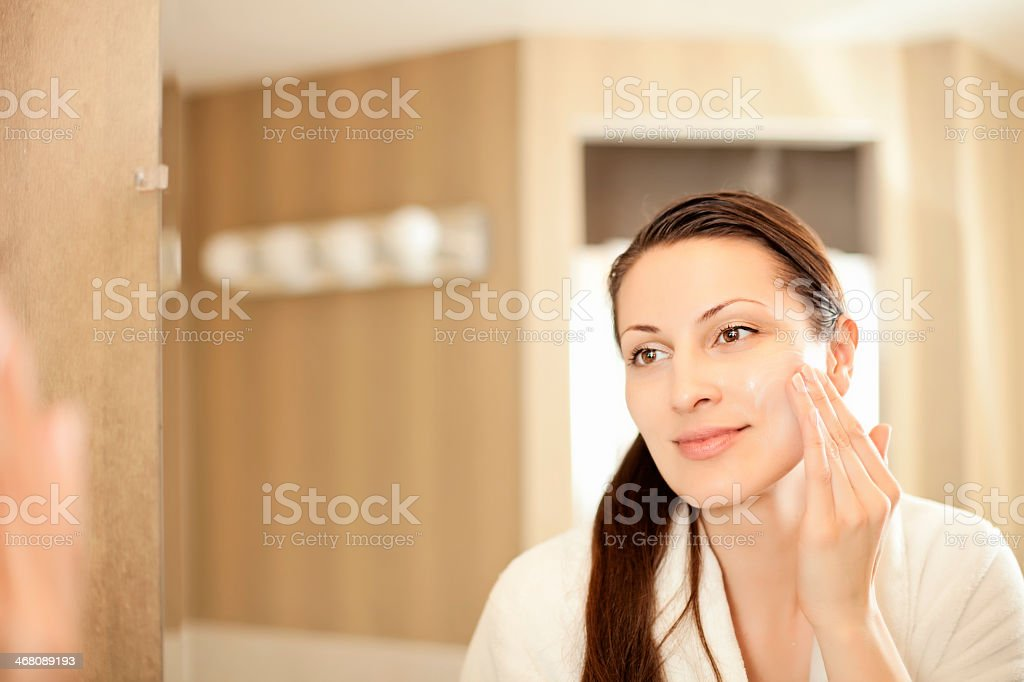 Woman applying cream to her face royalty-free stock photo