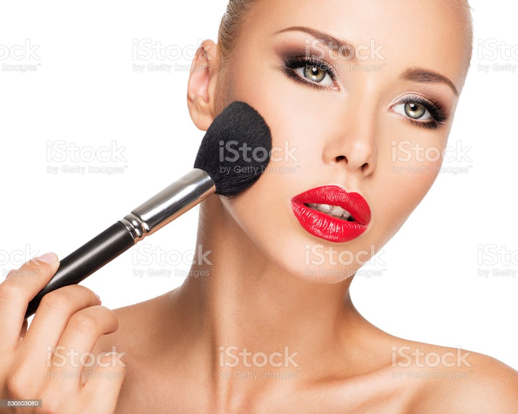 woman  applying dry cosmetic tonal foundation  on the face stock photo