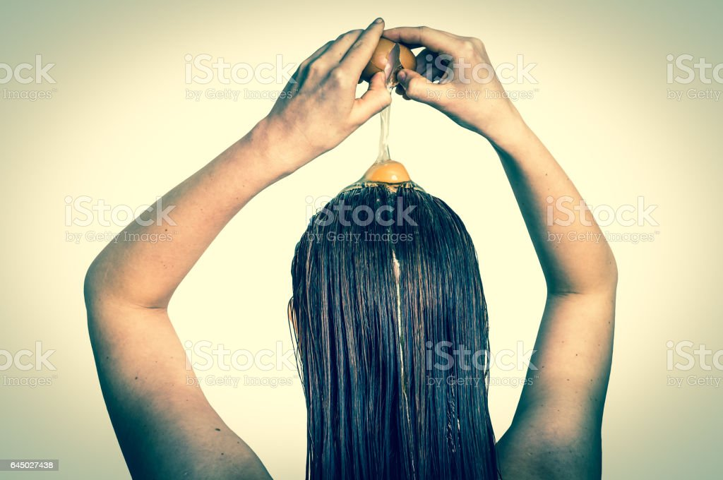 Woman applying egg conditioner on her hair stock photo