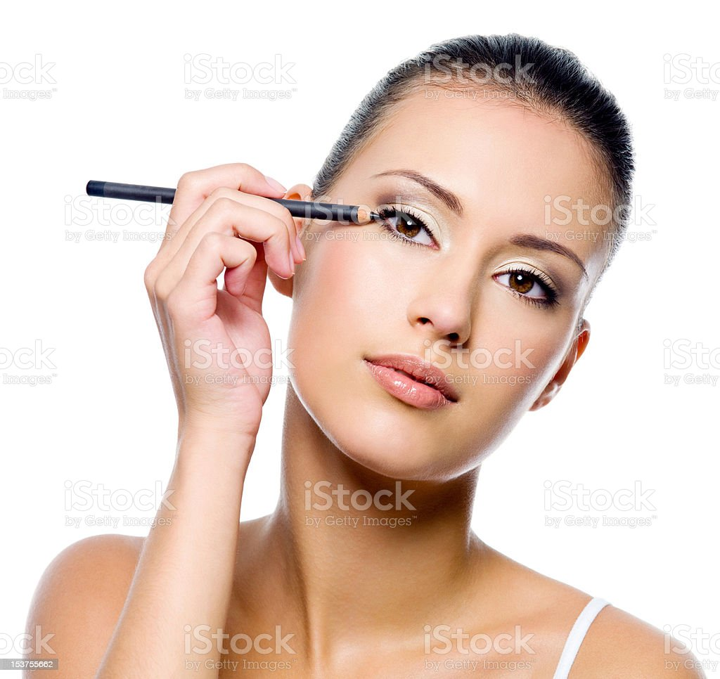 woman applying eyeliner on eyelid with pensil stock photo