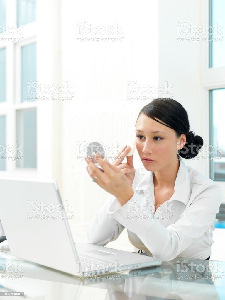 Woman applying face powder at royalty-free stock photo