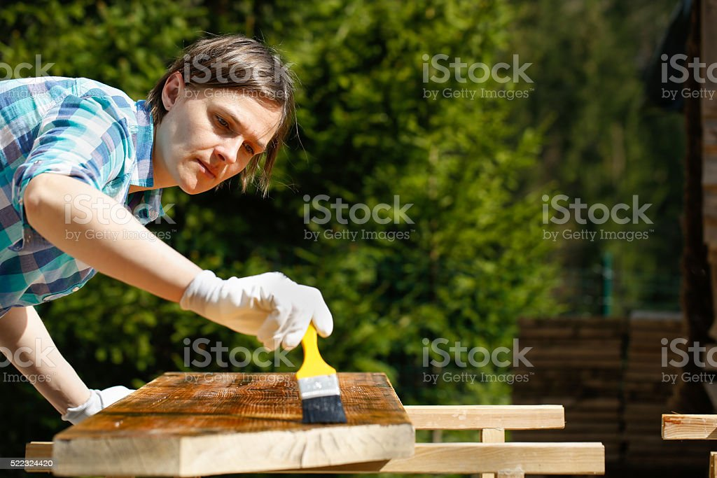 Woman applying fresh wood treatment paint stock photo