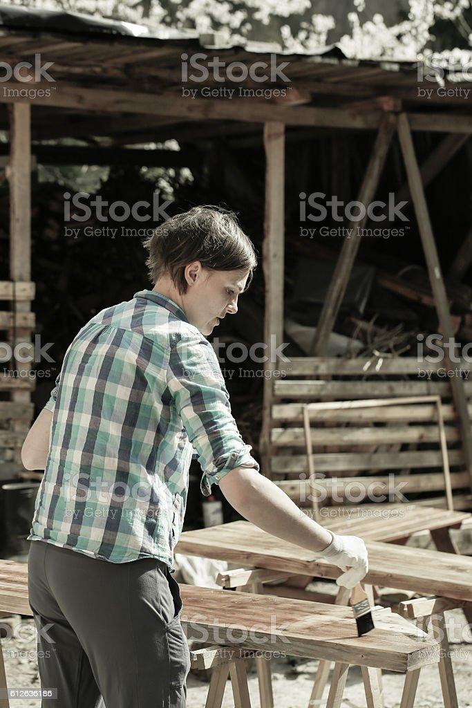 Woman applying fresh wood treatment paint stock photo