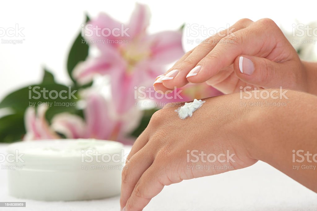 Woman applying hand creme, stargazer lilies in background. royalty-free stock photo