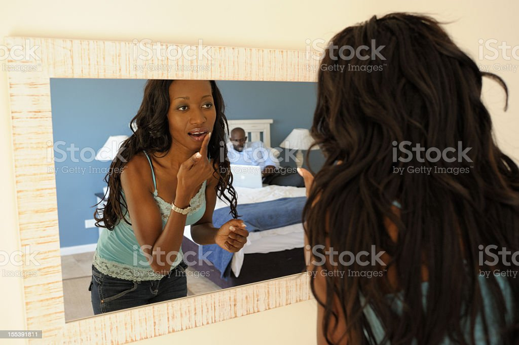 Woman Applying Lip Gloss While Looking in Mirror stock photo