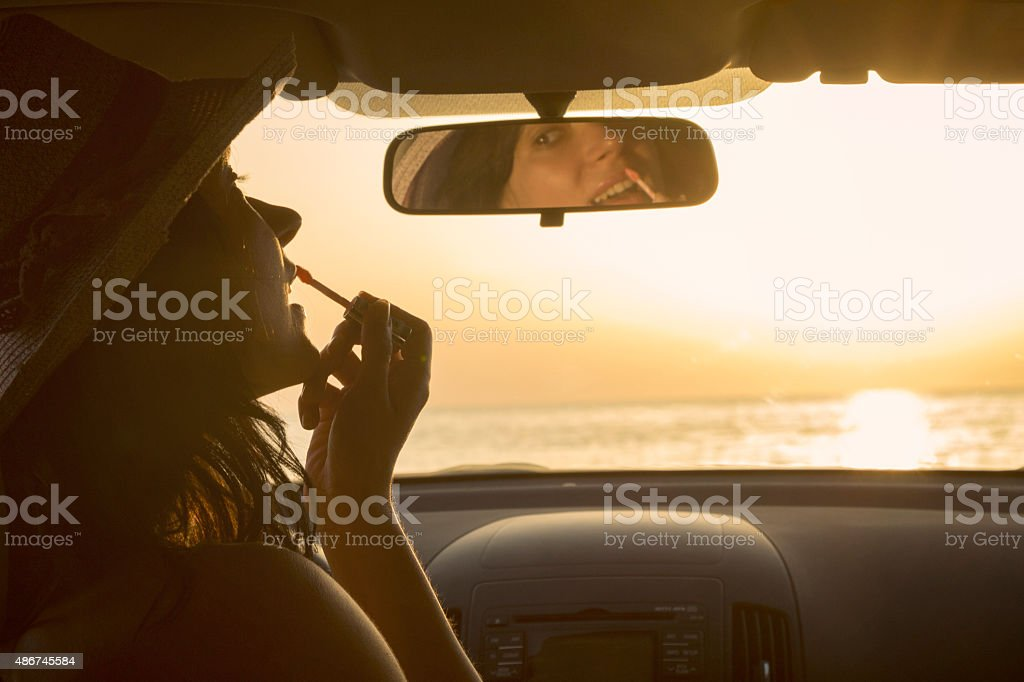 Woman applying lipstick and using rearview mirror in car stock photo