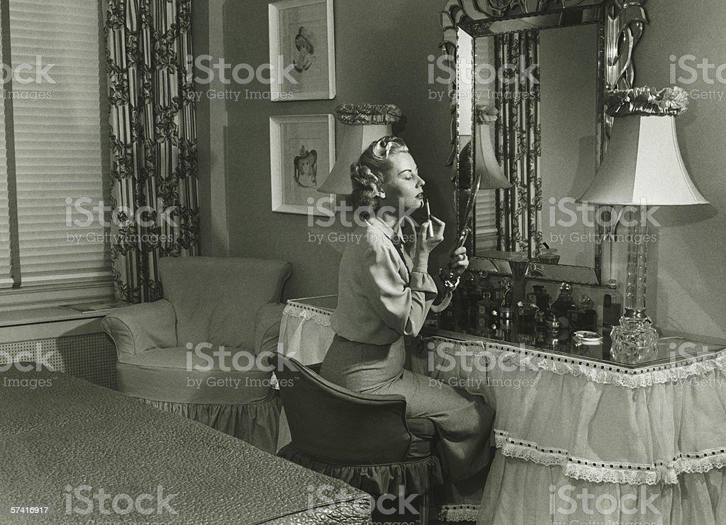 Woman applying lipstick at vanity table, (B&W) stock photo