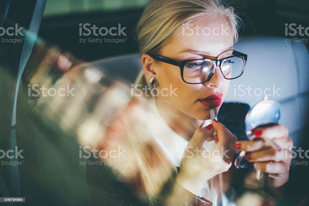 Woman applying lipstick in a car stock photo