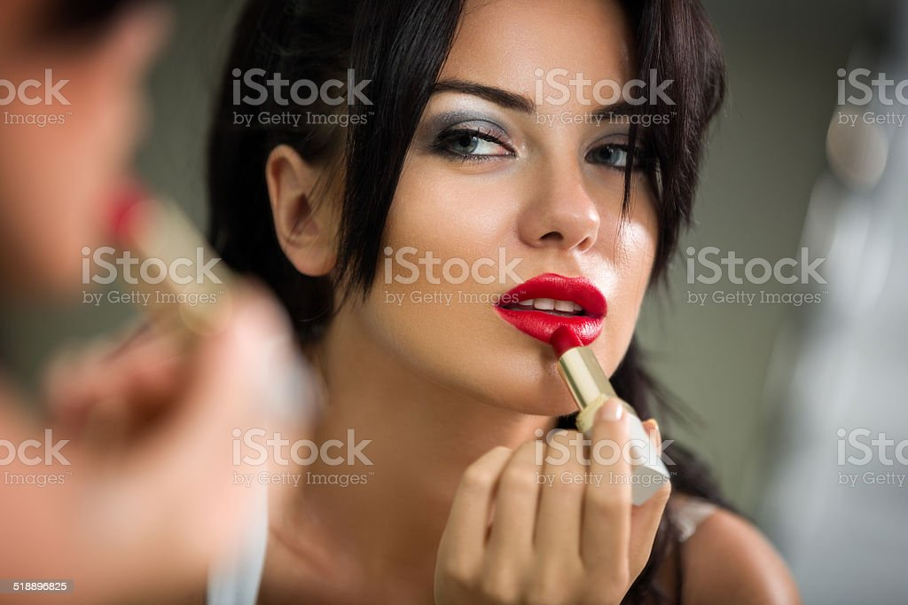 woman applying lipstick looking at mirror stock photo