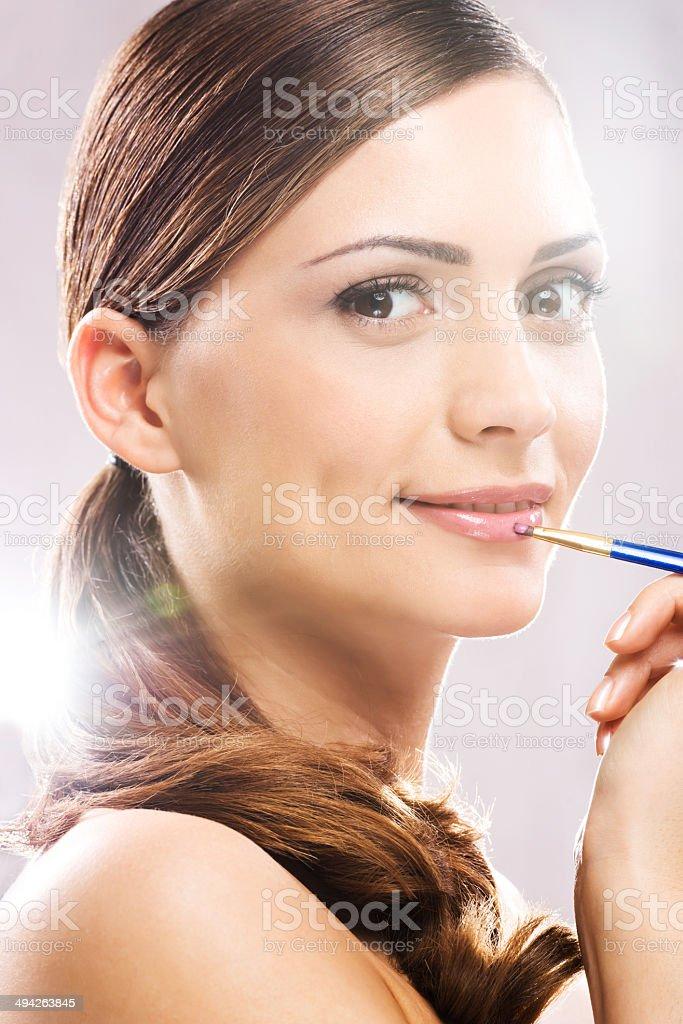 Woman applying lipstick. stock photo