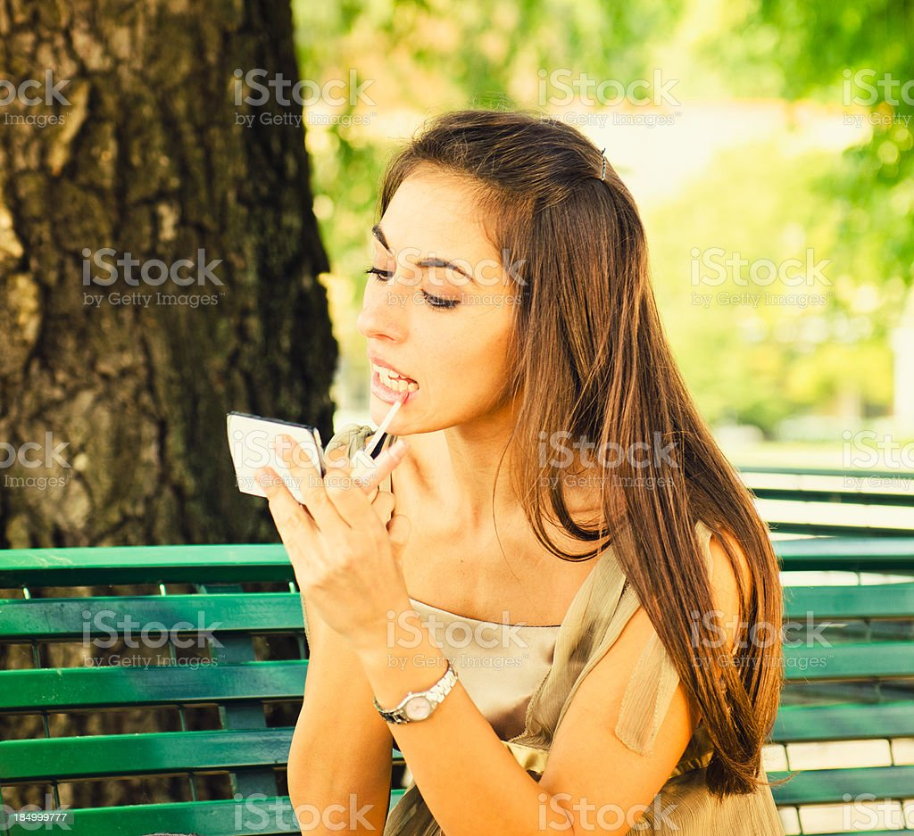 Woman applying make up during a break stock photo