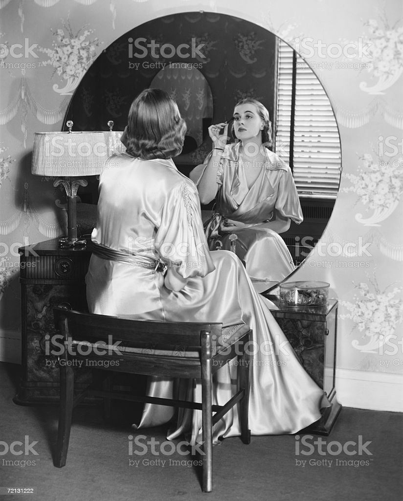 Woman applying make up in front of vanity table,  (B&W), stock photo