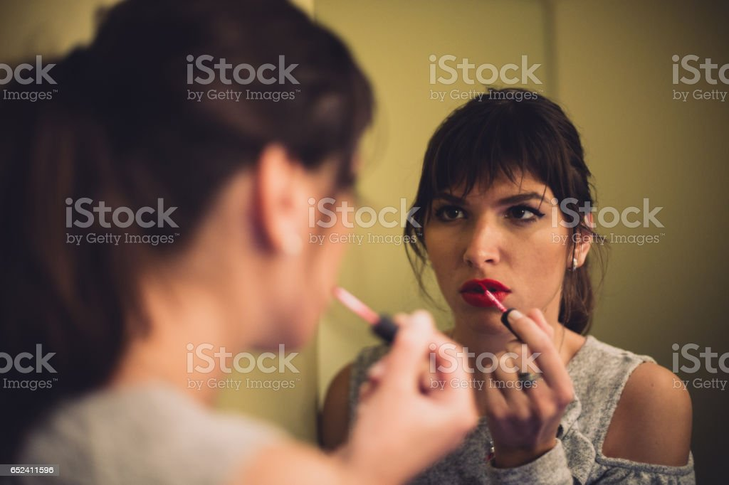Woman applying make-up in toilette stock photo