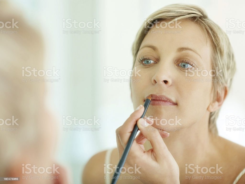 Woman applying makeup looking at the mirror stock photo