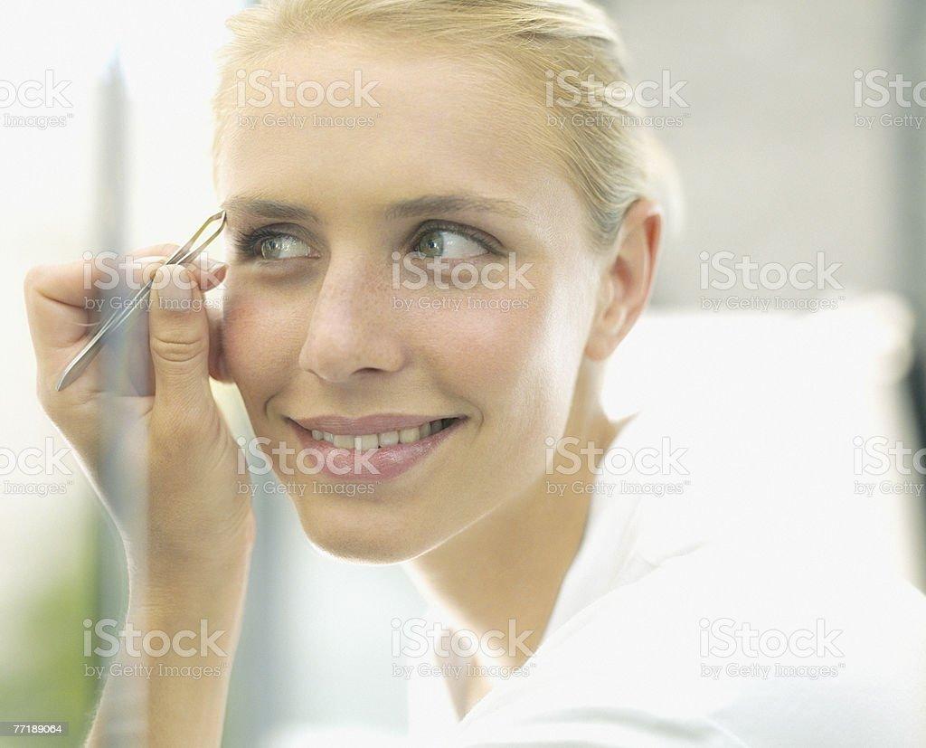 A woman applying make-up royalty-free stock photo