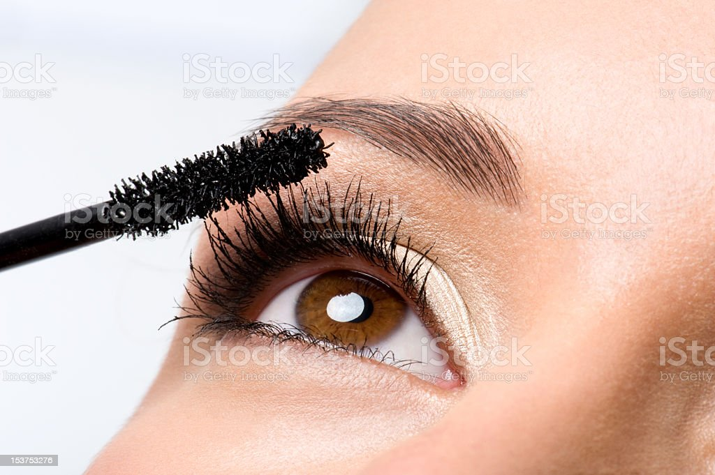 Woman applying mascara on eyelashes stock photo