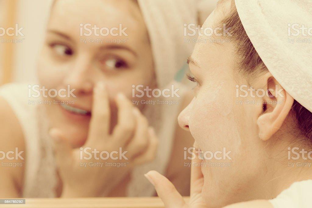 Woman applying mask cream on face in bathroom stock photo