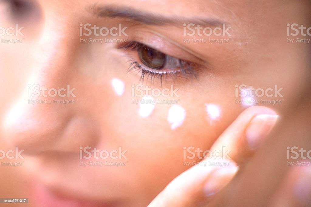 Woman applying moisturiser on face stock photo