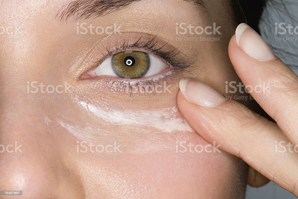 Woman applying moisturiser stock photo
