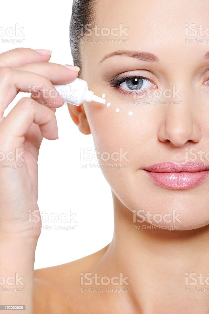 Woman applying moisturizer cosmetic on her eyelid royalty-free stock photo