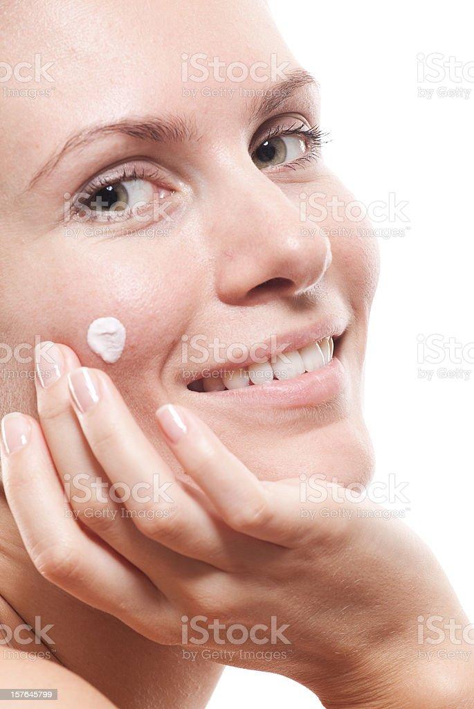Woman applying moisturizer cream on face. royalty-free stock photo