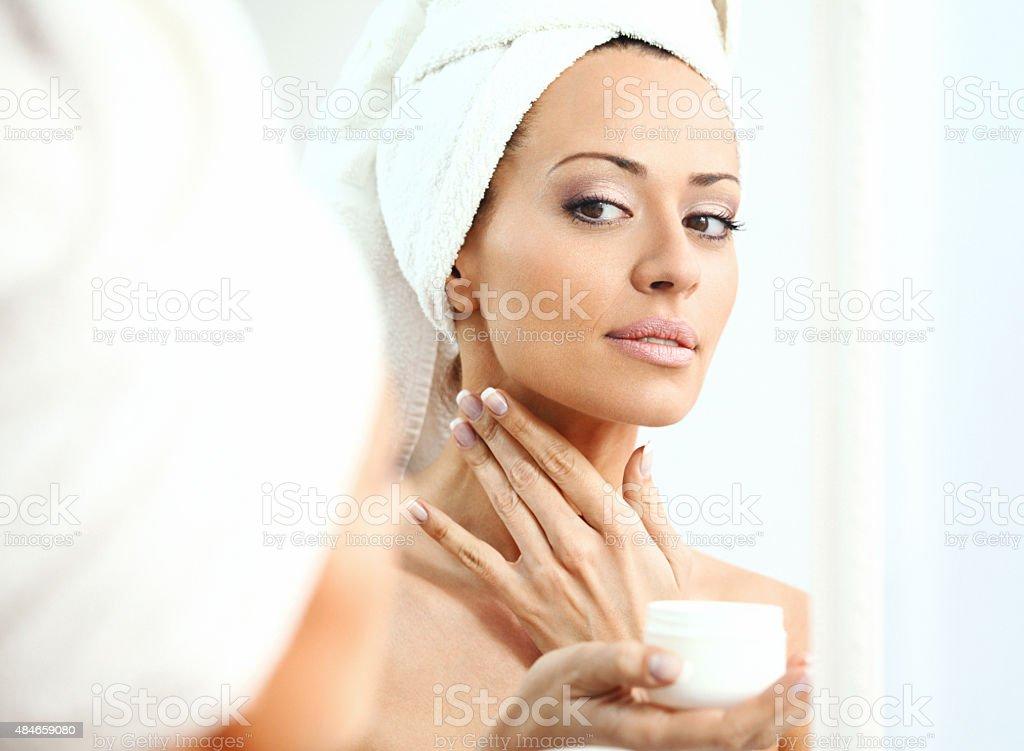 Woman applying moisturizer onto her neck stock photo