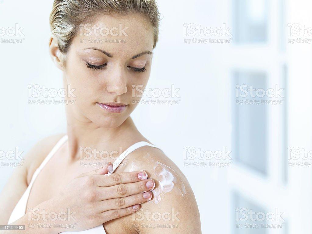 Woman applying moisturizer royalty-free stock photo