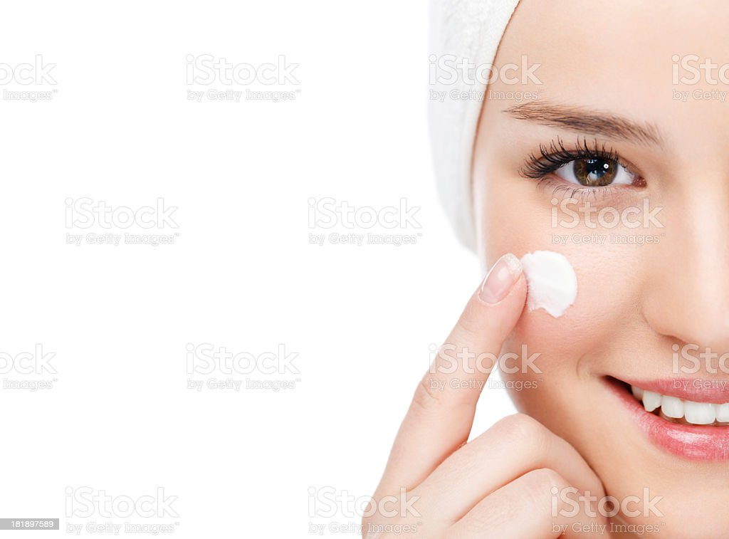 Woman applying moisturizer stock photo