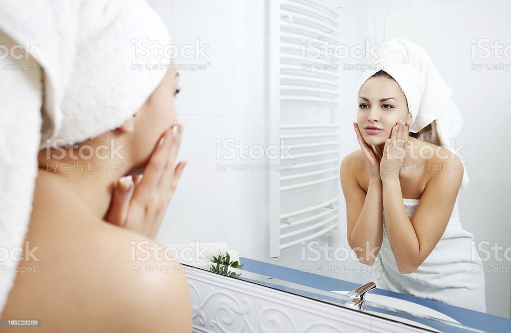 Woman applying moisturizer to her face. stock photo