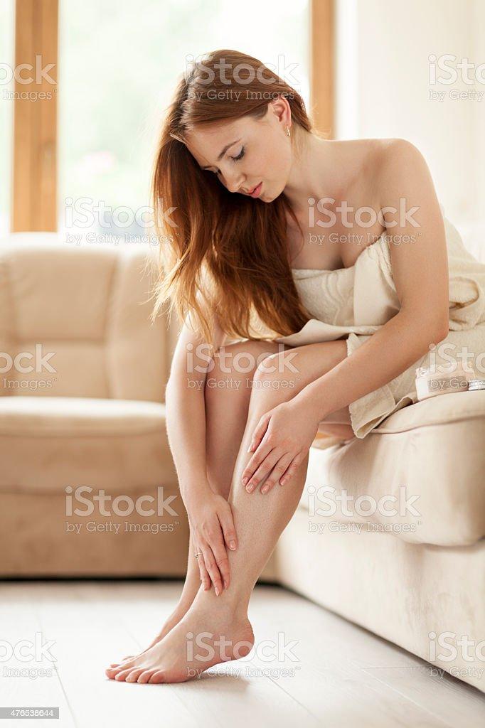 Woman Applying Moisturizer To Her Legs stock photo