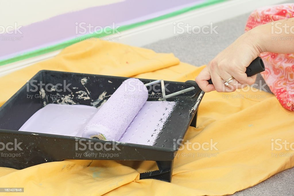 Woman Applying Paint to a Paint-Roller stock photo