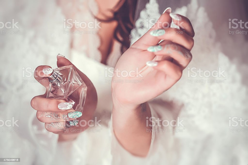 woman applying perfume on her wrist stock photo