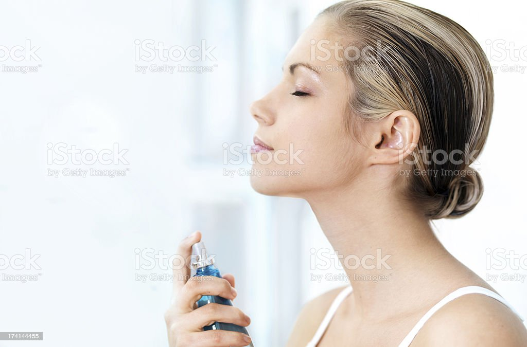 Woman applying perfume stock photo