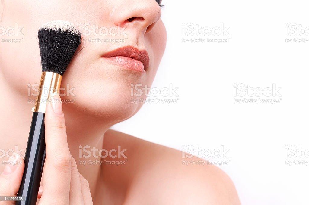 Woman applying powder make up with thick black brush royalty-free stock photo