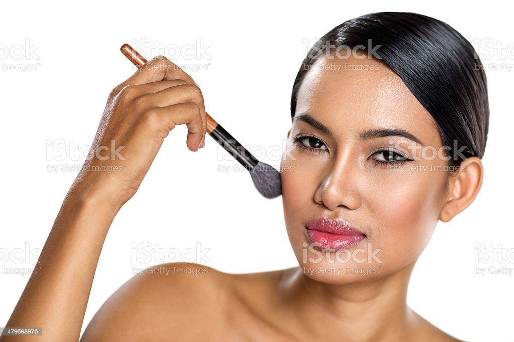 woman applying powder on cheek stock photo