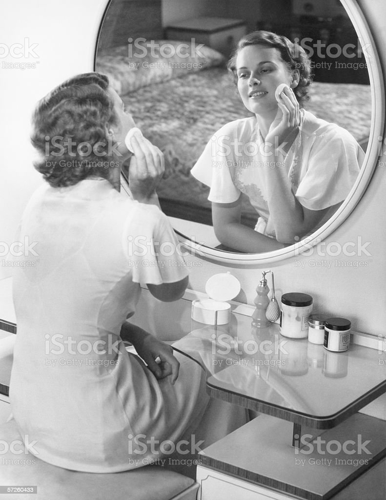 Woman applying powder with powder puff in front of mirror, (B&W) stock photo