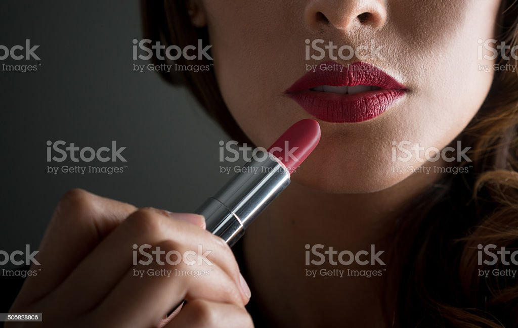 Woman applying red lipstick stock photo