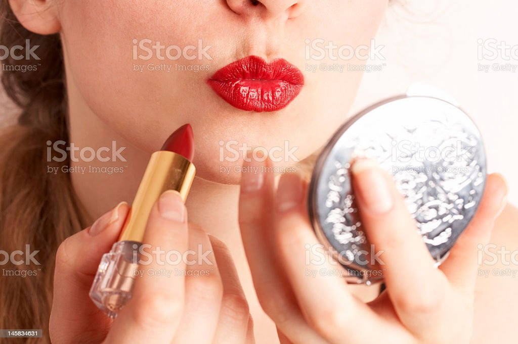 Woman applying red lipstick while looking to hand mirror stock photo