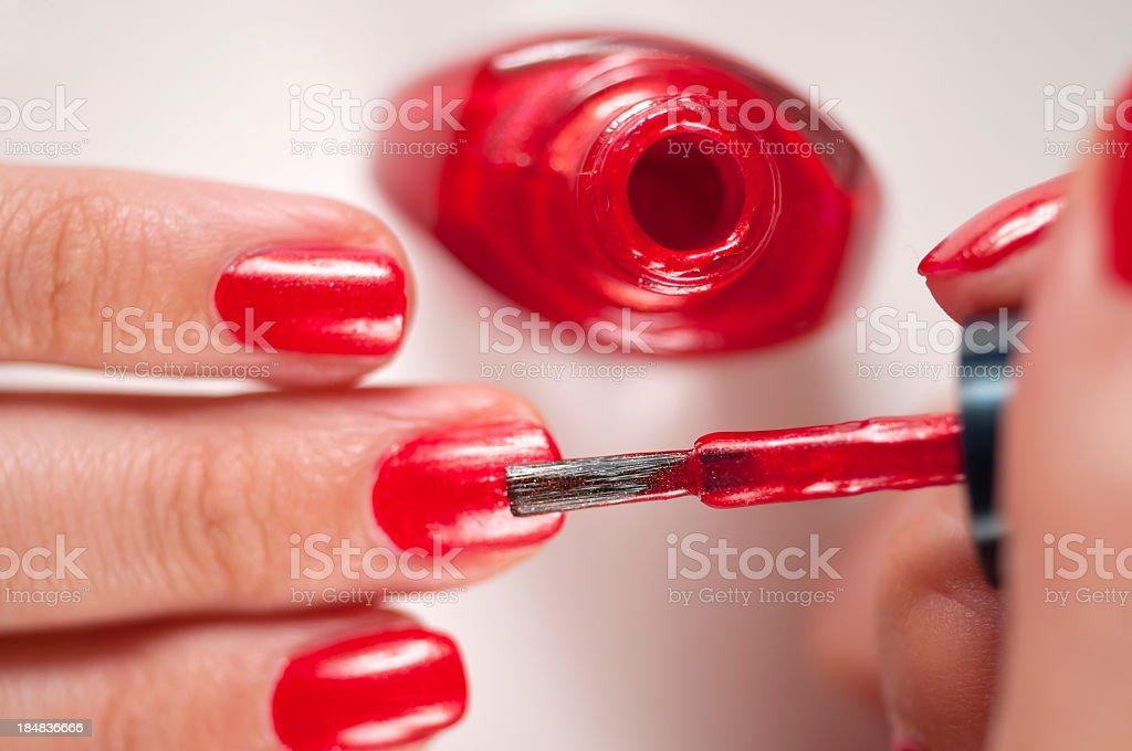 A woman applying red nail polish stock photo