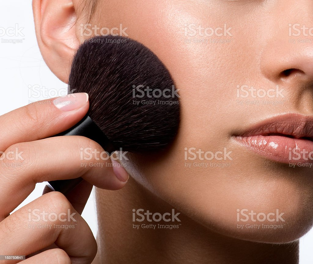woman applying rough on cheek stock photo