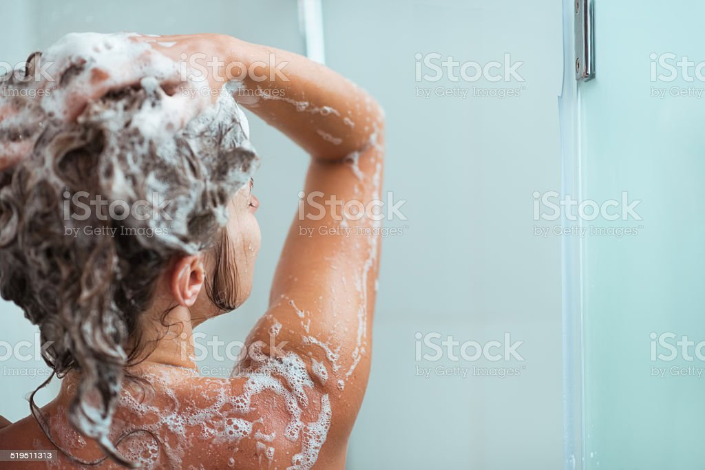 woman applying shampoo in shower. rear view stock photo