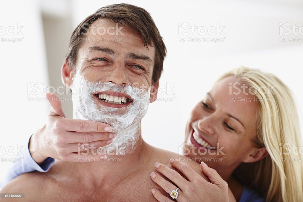 Woman applying shaving cream on man's face royalty-free stock photo