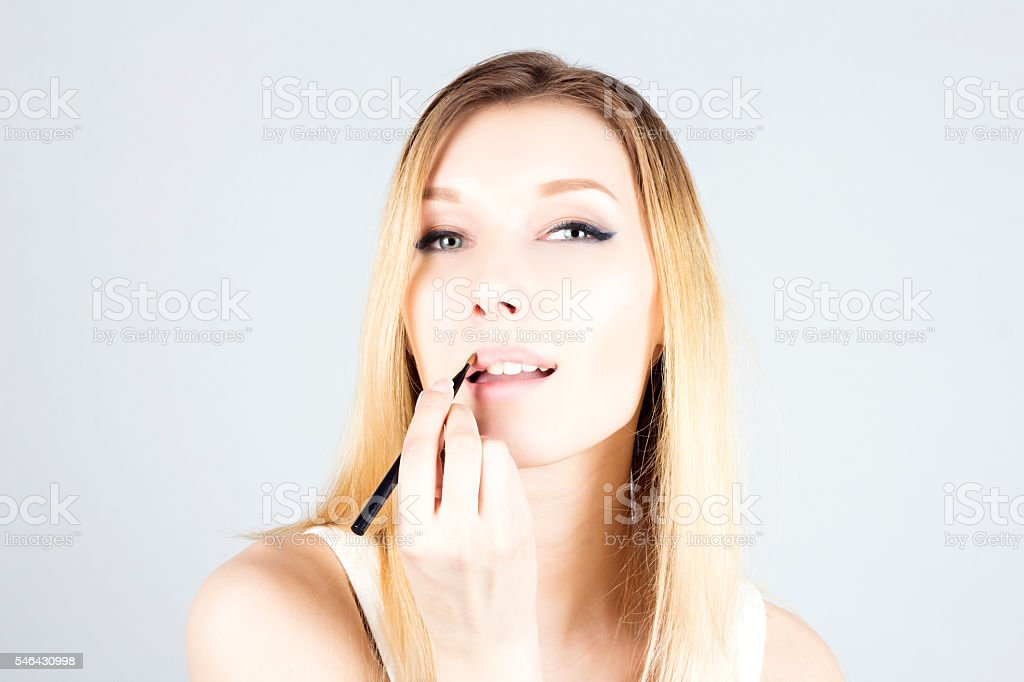 Woman applying shine on her lips with a brush. Make-up stock photo