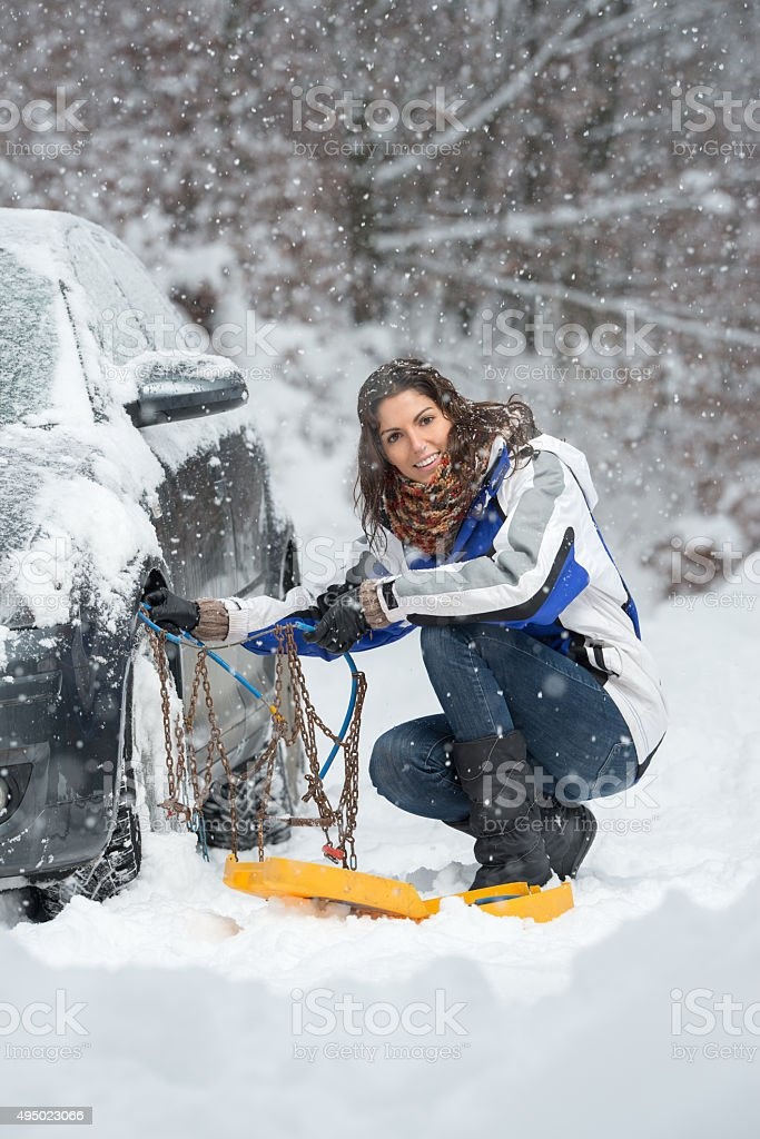 Woman applying Snow Chains, Heavy Snow Fall stock photo