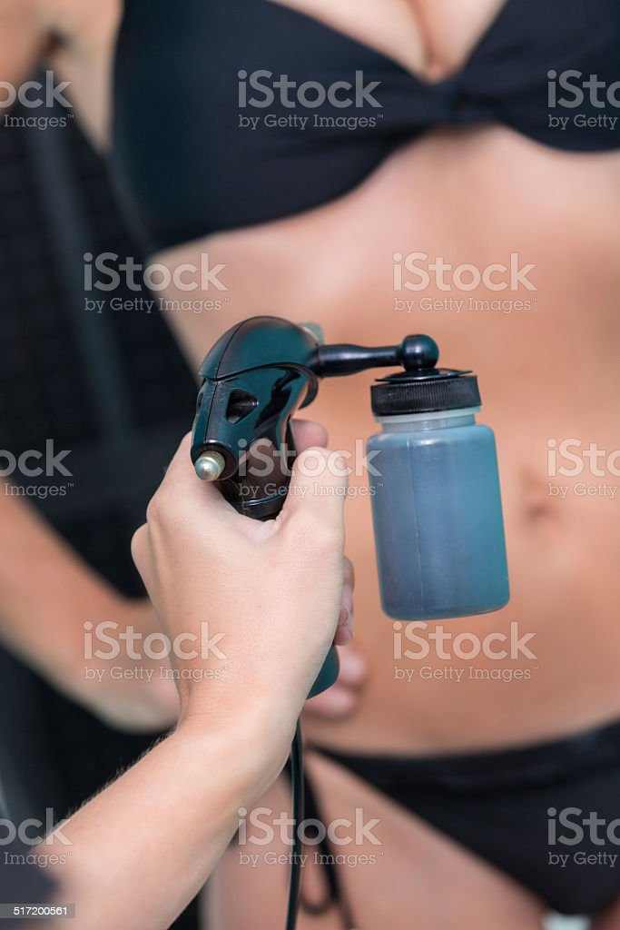 Woman applying spray tan to spa customer stock photo