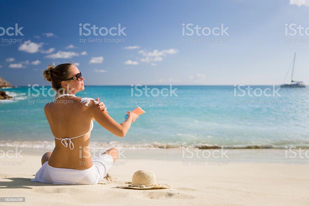 woman applying sunscreen at the beach stock photo