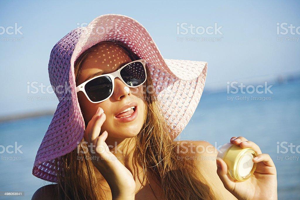 Woman applying sunscreen stock photo